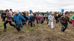 Flera barn springer mot kameran och ler under en dag med Vattenfall och Klimatbacken