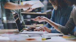 bild på en dator och personer som jobbar runt datorn