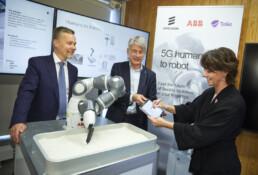 Två män och en kvinna står framför en lite robot