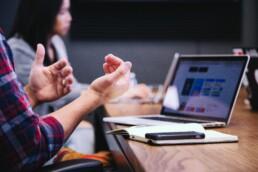 Gestikulerande händer framför en laptop